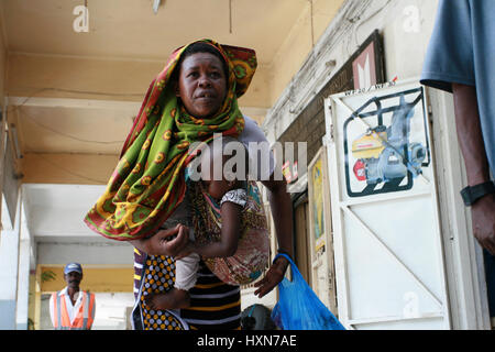 Dar es Salaam, Tanzania - February 21, 2008: Black African woman with an infant in a sling. - Stock Photo