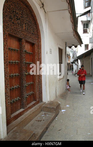 Zanzibar, Tanzania - February 16, 2008: Vintage traditional carved wooden doors in the houses on the narrow streets - Stock Photo