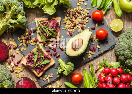 Healthy vegan food. Sandwiches and fresh vegetables on wooden background. - Stock Photo