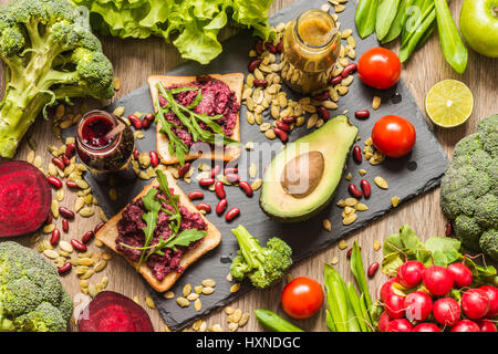 Healthy vegan food. Sandwiches and fresh vegetables on wooden background. Detox diet. Different colorful fresh juices - Stock Photo