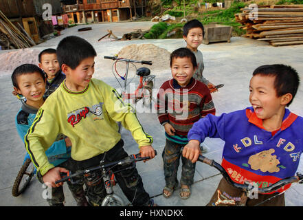 GUIZHOU PROVINCE, CHINA - APRIL 8: Rustic, Chinese boys sit on the bikes and laugh, April 8, 2010. Zhaoxing village, - Stock Photo