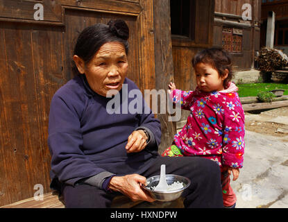 GUIZHOU PROVINCE; CHINA - APRIL 8: Dong ethnic old woman feeds child of three years by house in Zhaoxing Dong Village, - Stock Photo