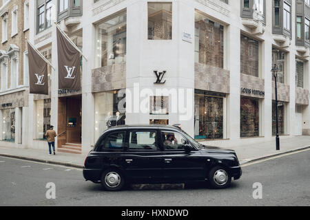 Transport: A black London cab / taxi drives past the Louis Vuitton Shop in Bond Street. - Stock Photo