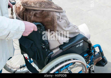 Elderly lady in wheelchair being pushed by carer or assistant. - Stock Photo