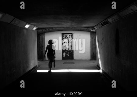 silhouette of woman walking alone through a tunnel - Stock Photo