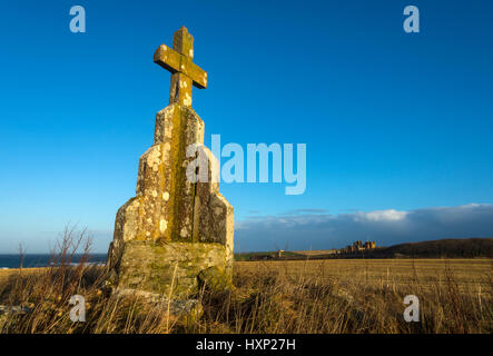 Stone cross on the Cairn of Mey, near the village of Mey, Caithness, Scotland, UK. Castle of Mey in the distance. - Stock Photo