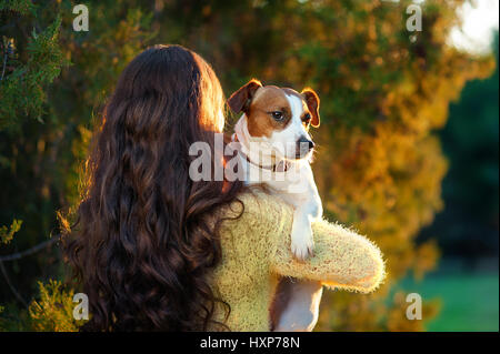 Young woman with beautiful long hair is standing with her back and is holding a Jack Russell terrier on her shoulder - Stock Photo