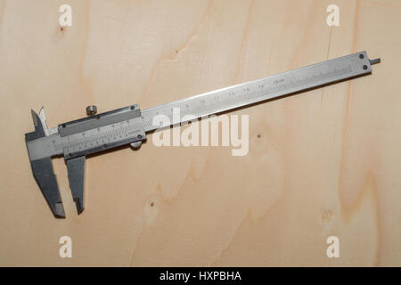 Measuring instrument calliper on a wooden surface - Stock Photo