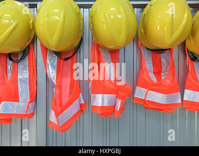New helmet and jacket set is hanging on the office wall for foreman use in the construction site. - Stock Photo
