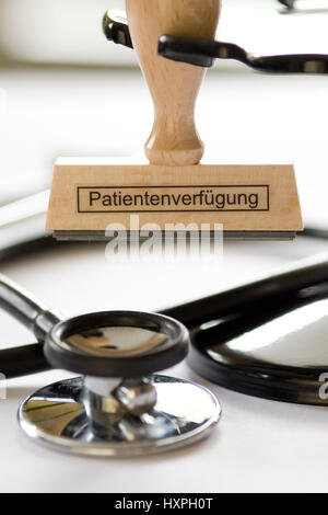 Stamp with label Patient's possession hangs on stamp circular flower bed before a Stethoskop, Stempel mit Aufschrift - Stock Photo