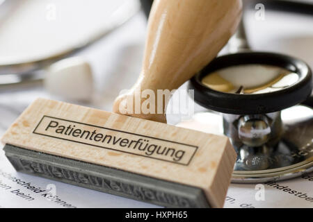 Stamp with label Patient's possession lies on health insurance scheme documents and a Stethoskop, Stempel mit Aufschrift - Stock Photo