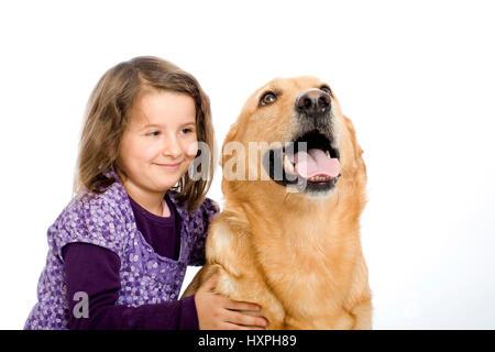 6-year-old girl cuddles retriever's schnauzer hybrid, (mr), sechsjähriges Mädchen schmust mit Retriever-Schnauzer - Stock Photo
