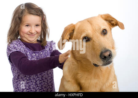 6-year-old girl cuddles retriever's schnauzer hybrid (mr), sechsjähriges Mädchen schmust mit Retriever-Schnauzer - Stock Photo