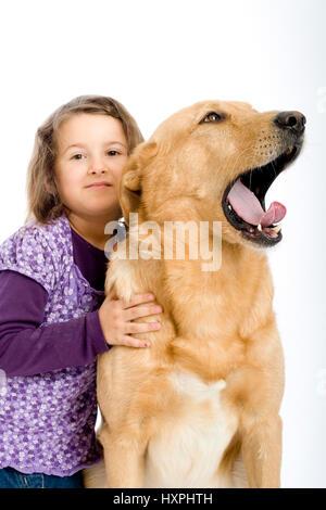 6-year-old girl cuddles retriever's schnauzer hybrid, sechsjähriges Mädchen schmust mit Retriever-Schnauzer-Mischling - Stock Photo
