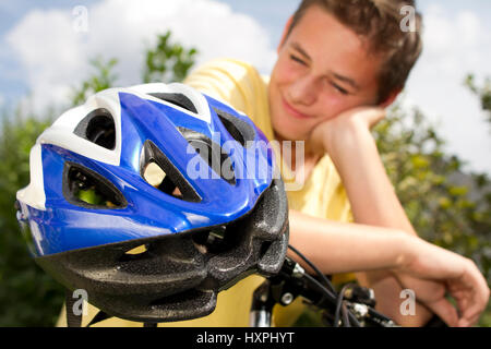 Teenager against bicycle helmet, Teenager gegen Fahrradhelm - Stock Photo