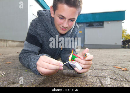 Youngster with New Year's Eve saluting gun, Jugendlicher mit Silvesterböller - Stock Photo
