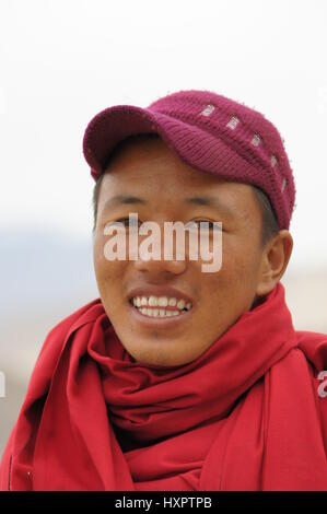 A photo of a young Buddhist novice who was taking the entrance fee at the Namgyal Tsemo gompa in Leh, Kashmir. - Stock Photo