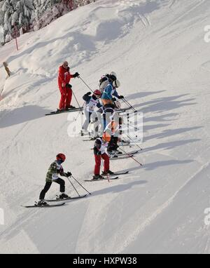 Ski school lined up on a steep piste, Les Contamines, Savoie, France, February. - Stock Photo