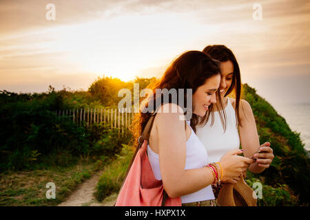 Happy young female friends watching something in the smartphone on a cliff at sunset - Stock Photo