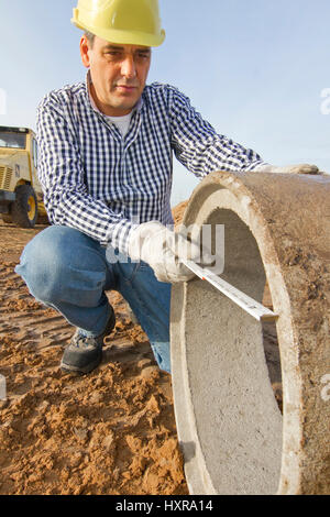 Construction worker works with pipe, Bauarbeiter arbeitet mit Rohr - Stock Photo