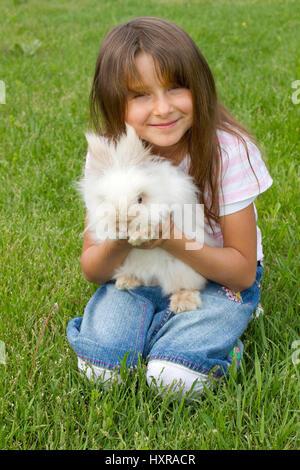 seven-year-old girl with Teddy's pygmy rabbit, siebenjähriges Mädchen mit Teddyzwergkaninchen - Stock Photo