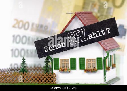 Miniature house with GEZ slogan Already Paid? Fees GEZ per household, Miniaturhaus mit GEZ-Slogan Schon GEZahlt? - Stock Photo