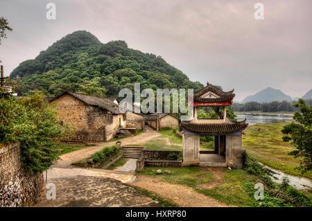 Fuli Village, Yangshuo, Guangxi, China - March 30, 2010: Stone pagoda pergola at the entrance to the mountain village - Stock Photo