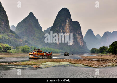 Yangshuo, Guangxi, China - March 29, 2010: Cruise ship packed with tourists travels the magnificent scenic route - Stock Photo