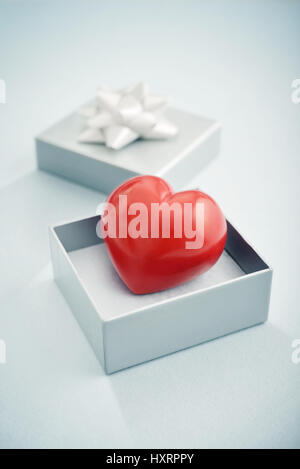 Red stone heart in silver gift box on blue background - Stock Photo