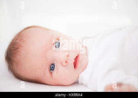 Cute adorable newborn baby girl in white bed and looking at the camera - Stock Photo