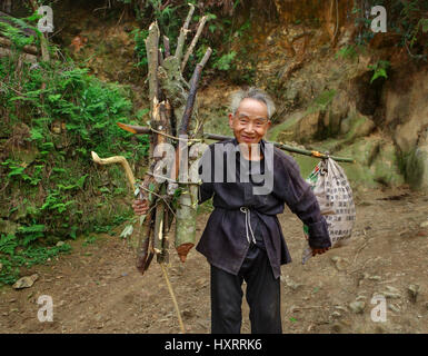 Zengchong village, Guizhou, China - April 11, 2010: An elderly Chinese man goes on a mountain road with a load on - Stock Photo