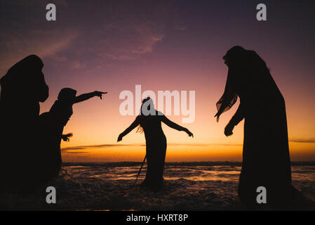 Galle Face Green in Colombo Sri Lanka.  Families gather for sunset and play in the ocean together.  Here Muslim - Stock Photo