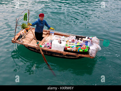 Vietnamese woman offers goods for sale on Ha Long Bay - Stock Photo