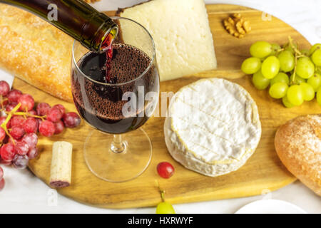 Red wine poured into a glass at a tasting, with various types of cheeses, bread, and grapes. Selective focus - Stock Photo