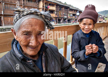 Zhaoxing Dong Village, Guizhou Province, China -  April 8, 2010: Elderly Asian women are resting on a bench in the - Stock Photo