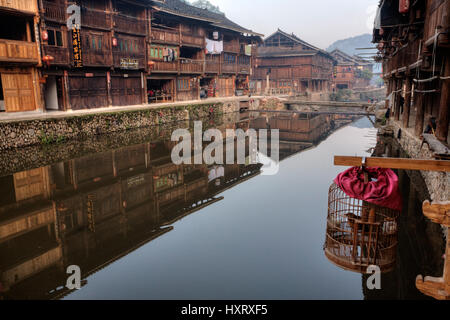 Zhaoxing Dong Village, Guizhou Province, China -  April 9, 2010: Wooden houses of farmers reflected in the water - Stock Photo