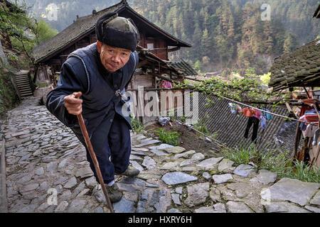 Langde Village, Guizhou, China - April 15, 2010:  Langde Miao ethnic minority village, Old Chinese man walking along - Stock Photo