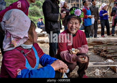 Langde Village, Guizhou, China - April 16, 2010: Chinese woman with a rose in her hair smiling at the village festival - Stock Photo