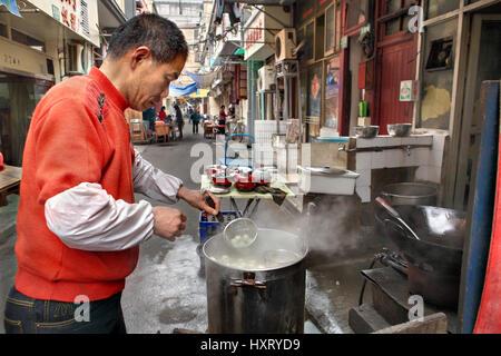 Shanghai, China - April 20, 2010: Seller street food, outdoor, cooking dumplings in a big pot - Stock Photo