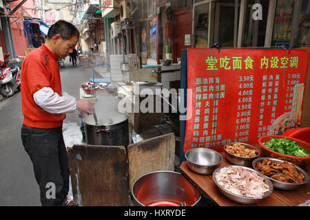 Shanghai, China - April 20, 2010: Outdoor eatery in the open, the chef prepares food on the street. - Stock Photo