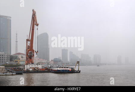 Shanghai, China - April 20, 2010: Air pollution in City, Floating crane near the Bund during a polluted day, Buildings - Stock Photo