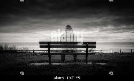 Ghostly figure sitting on a park bench - Stock Photo