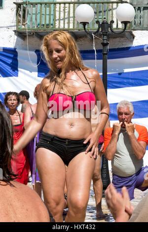 tanzende blonde Frau in Bikini vor griechischer Fahne und Strassenlaterne, Insel Kastellorizo, Dodekanes, Griechenland - Stock Photo