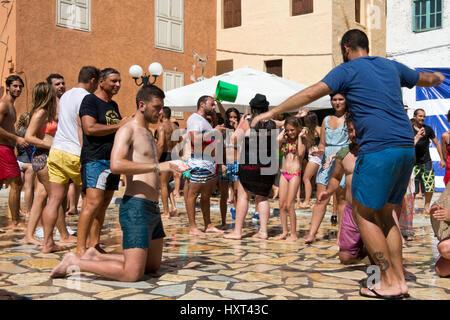 tanzende Menschen in Badekleidung auf Dorfplatz, dahinter farbige Häuser und griechische Fahne, Insel Kastellorizo, - Stock Photo