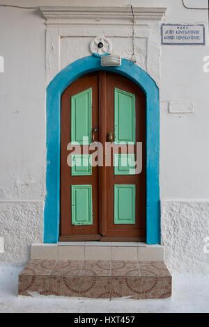hölzerne Eingangstüre hellgrün und braun mit türkiser Einfassung in weißer Fassade, Insel Kastellorizo, Dodekanes, - Stock Photo