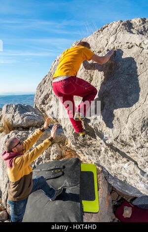 Back view of man climbing rock bouldering. Roao, Villanueva del Rosario, Malaga. - Stock Photo