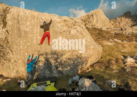 Back view of people climbing rock boulder in sunset. Roao, Villanueva del Rosario, Malaga - Stock Photo