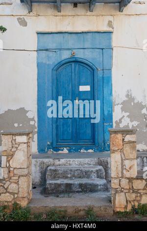 alte blaugestrichene hölzerne Eingangstüre mit Stufen und blauer Einfassung in weißem Haus, Insel Kastellorizo, - Stock Photo