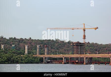 Construction of tall concrete piers using tower crane for new bridge across Mondovi River in Goa, India - Stock Photo