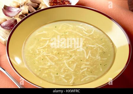 en plato redondo amarillo sopa de pasta con frutos secos - Stock Photo